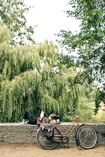 Woman Reading Beside Her Bicycle in Amsterdam